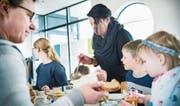 Besucher geniessen die Mais-Rüebli-Erbsensuppe in geselliger Runde am grossen Tisch. (Bild: Andrea Stalder)