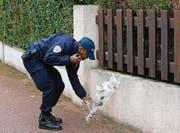 Im Gedenken an den ermordeten Berufskollegen: Ein Polizist legt am Tatort eine Blume nieder. (Bild: ap/Thibault Camus)