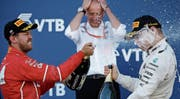 Sebastian Vettel duscht seinen Bezwinger Valtteri Bottas. (Bilder: Pavel Golovkin/AP)