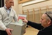 Stimmenzähler Herbert Mazur sammelt mit der Urne die Zettel ein. (Bild: Stefan Hilzinger)