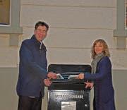 Robin Alder, Präsident der Arbeitgebervereinigung, und Paula Looser, Bibliotheksleiterin, beim neuen Medienrückgabekasten. (Bild: PD)