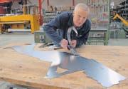 Fast wie ein Scherenschnitt: Kurt Zwingli schneidet mit der Metallschere das 0,75 Millimeter dünne Stahlblech für den Brutfuederträger. (Bild: Hansruedi Kugler)