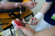 Lebenswichtiger «Rohstoff»: Eine Mitarbeiterin des Blutspendedienstes nimmt einem Spender das Blut ab. (Bild: Ralph Ribi)
