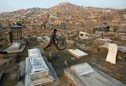 Afghanische Alltagsszene: Ein Bub spielt mit einem Reifen auf einem Friedhof in einem Kabuler Aussenquartier. (Bild: Rahmat Gul/AP)