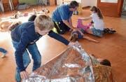 Im Nothilfekurs mit Globi lernen die Kinder von Sabina Pipping, wie man Bewusstlose seitlich lagert und warmhält. (Bild: Hanspeter Thurnherr)