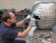 Der Zuzwiler Apfel gedeiht: Künstler Alf Suter bei der Gestaltung der künstlichen Frucht aus circa 700 verschieden grossen Blechteilchen.