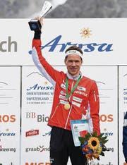 Daniel Hubmann stemmt in Arosa nach seinem grossen Triumph den Pokal in die Höhe. (Bild: ky/Gian Ehrenzeller)