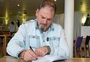 René Hengartner signiert in der Rehaklinik Zihlschlacht seine Geschichte im Buch «Sieben Leben». (Bild: Yvonne Aldrovandi-Schläpfer)