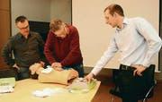 Wie macht man eine Herzmassage? Erlens Gemeindeammann Roman Brülisauer und Bauverwalter Jörg Bürgisser folgen den Instruktionen von Marc Wettering. (Bild: Hannelore Bruderer)