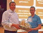 FDP-Präsident Simon Seelhofer (rechts) bedankt sich mit einem Präsent bei Referent Glen Aggeler. (Bild: Peter Jenni)