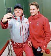 Ein freiwilliger Helfer hält in Pyeongchang sein Treffen mit Fabian Bösch fest. Der 20-jährige Schweizer sagt: «Das Ziel ist das Podest.» (Bild: Jean-Christophe Bott/KEY)
