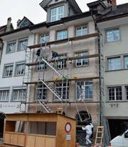 Die Maler bauen das Baugerüst wieder ab. Die untere Hälfte befindet sich noch im ursprünglichen Zustand. Oben wurde die Fassade für den neuen Anstrich vorbereitet. (Bild: Gianni Amstutz (11. Dezember 2017))
