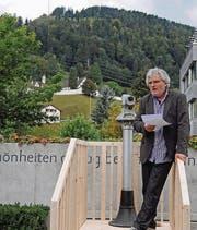 Leo Morger spricht an der Vernissage. Mit dem Fernrohr kann die Mauerveränderung vom Bräkerplatz aus betrachtet werden. (Bild: Michael Hug)