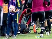 Besiktas-Coach Senol Günes krümmt sich nach dem Messerwurf vor Schmerz auf dem Rasen (Bild: KEYSTONE/EPA/SEDAT SUNA)