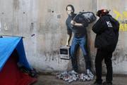Das neuste Werk von Banksy am Eingang des Flüchtlingscamp in Calais. (Bild: AP Photo/ Michel Spingler)