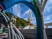 Im Unterengadin manipulierten Bauunternehmen über Jahre hinweg Beschaffungen im Hoch- und Tiefbau. Die Wettbewerbskommission hat sieben Firmen mit insgesamt rund 7,5 Millionen Franken gebüsst. (Symbolbild) (Bild: Keystone/OLIVIER MAIRE)