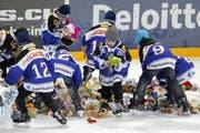 EVZ-Junioren sammeln die Plüschtiere ein, die zugunsten einer wohltätigen Aktion aufs Eis geworfen wurden. (Bild: Keystone)