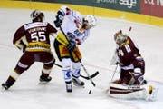 Sven Senteler, Mitte, wurde beim Spiel vom 7. März von Genfs Daniel Vukovic, links, mit dem Stock geschlagen. (Bild: KEYSTONE)