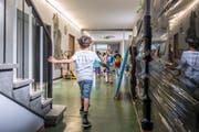 """Letzter Schultag im Schulhaus Tschudiwies vor den Sommerferien 2017: Aus und vorbei. Schulkinder neben zügelbereiten Paletten in einem Korridor ihres alten Schulhauses. Ab Herbst gehen sie im """"St.Leonhard"""" zur Schule. (Bild: Urs Bucher - 7. Juli 2017)"""