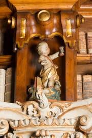 Der Arzt mit den Attributen Uringlas, Medizinflasche und Büchern. Putte im Barocksaal der Stiftsbibliothek St.Gallen um 1770. (Bild: Stiftsbibliothek St.Gallen)