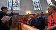 Karin Müller referiert über die Kirchenfenster. Auch Pfarrer Lukas Butscher und seine Frau Fiona (zweite Reihe) hören zu. (Bild: Manuel Nagel)