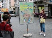 Die jungen Gestalter erläutern in der Marktgasse, wie sie den «Fadian» in ihre Werke eingearbeitet haben. (Bild: Michael Zwimpfer)