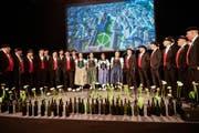"""Das Jodelchörli St.Gallen Ost führt in der Olma-Halle 2.1 die neue Jodelhymne """"Mini Heimatstadt"""" auf. Dies passend vor einem Bild mit dem Klosterbezirk und der der südlichen Altstadt. (Bild: Ralph Ribi)"""