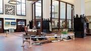 Arbeiter bauen in der Bahnhofhalle eine neue Sitzbank zusammen. (Bild: David Gadze)
