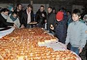 Die Bevölkerung greift gerne zu beim Dreikönigskuchen, den die Gemeinde am Samstag aufgetischt hat. (Bild: Ramona Riedener)