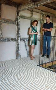 «Wer die Arbeit macht» im Haus zur Glocke, Steckborn: Kuratorin Judit Villiger und Künstler Othmar Eder stehen auf einer Bodenarbeit Werner Widmers. (Bild: Dieter Langhart)