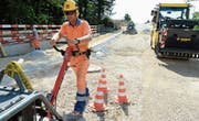 Polier Ralf Schüssling planiert den Strassenbelag. Das gute Wetter trägt dazu bei, dass die Arbeiten planmässig voranschreiten. (Bild: Helio Hickl)