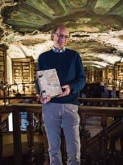 Karl Schmuki mit einer der Handschriften in der oberen Etage der Stiftsbibliothek. (Bild: Sabrina Stübi)