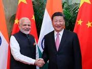 Indiens Regierungschef Narendra Modi (l) und Chinas Präsident Xi Jinping einigten sich auf eine friedliche Beilegung der Grenzstreitigkeiten zwischen den beiden Ländern. (Bild: KEYSTONE/AP Xinhua/JU PENG)