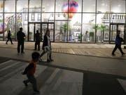 Passanten vor der Wanda Mall, einem Kaufhaus, das zur neu eröffneten Wanda Oriental Movie Metropolis in Qingdao, China, gehört - ein milliardenteurer Mega-Komplex, den Chinas reichster Mann Wang Jianlin finanziert hat. (Bild: Keystone/EPA/WU HONG)