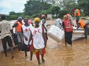 Rotkreuz-Helferinnen und -Helfer in Kenia mit Hilfsgütern für von Fluten betroffene Menschen (Bild: KEYSTONE/EPA/STR)