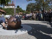 Die versiegelte Kupferkugel mit den Gedanken aus dem Bruder-Klaus-Gedenkjahr wird auf dem Dorfplatz von Flüeli in einen Schacht eingelassen. (Bild: Keystone/SIBYLLE KATHRINER FOTOGRAFIE)