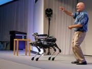 Boston Dynamics-Chef Marc Raibert mit dem vierbeinigen Roboter, der bald auf den Markt kommen soll (Bild: KEYSTONE/AP/SHIZUO KAMBAYASHI)
