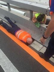 Voller Körpereinsatz: Die Polizisten der St.Galler Kantonspolizei bei der Rettung der Tiere auf der Autobahn. (Bild: Kapo SG)