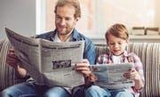 Wenn der Vater mit dem Sohn Zeitung liest ... Papi, was heisst Reform? Und: was bedeutet virtuell? (Bild: George Rudy/Getty)
