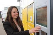 Postsprecherin Carmen Lama zeigt, wie der Paketautomat am Bahnhof Wil funktioniert. Post-Zugangspunkte wie dieser ersetzten Stück für Stück die herkömmliche Poststelle. (Bild: Simon Dudle)