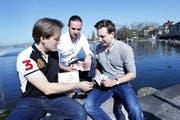 Die drei Unternehmer Marc Dür, Samuel Lutherbacher und Elio Reinschmidt mit ihrem Kartenspiel am Zugersee. Bild: Werner Schelbert (19. April 2018)