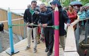 Felix Buschor und Werner Ackermann (von links) durchschneiden das grüne Band zur Eröffnung des Baumwipfelpfades. (Bild: Martin Knoepfel)