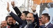 Anzug statt Schirmmütze und Tarnkleidung: Nikol Paschinjan tritt vor die jubelnde Menge auf dem Platz der Republik in Eriwan. (Bild: Thenassis Stavrakis/AP (8. Mai 2018))