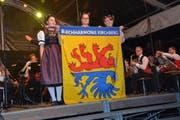 Die Ehrendamen Fabienne Häne, Lorena Segmüller und Martina Häne (von links) enthüllen die neue Vereinsfahne der Blechharmonie Kirchberg.Bilder: Beat Lanzendorfer (Bild: Beat Lanzendorfer)
