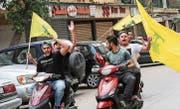 Hisbollah-Anhänger schwenken ihre Fahnen in einem Vorort Beiruts. (Bild: Nabil Mounzer/EPA (6. Mai 2018))