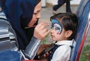 Ein Kind lässt sich während eines Strassenfests schminken. (Bild: Michael Wrase)