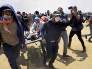 Während den blutigen Zusammenstössen im Gazastreifen an der Grenze zu Israel: Palästinensische Rettungskräfte und Protestierende transportieren einen schwerverletzten Jugendlichen auf einer Bahre. Der heutige Montag ist der Tag mit den meisten Todesopfern seit dem Gaza-Krieg 2014. (Bild: Keystone/AP/ADEL HANA)