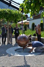 DIe Zeitkapsel auf dem Dorfplatz im Flüeli-Ranft wird vorsichtig in ihren zukünftigen Standort eingelassen. (Bild: Franziska Herger (Sachseln, 12. Mai 2018))