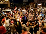 Anhänger schiitischen Predigers Moktada al-Sadr feiern auf den Strassen in Bagdad schon seinen Wahlsieg bei den Parlamentswahlen - obwohl das offizielle Endergebnis noch nicht feststeht. (Bild: KEYSTONE/AP/HADI MIZBAN)