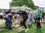 Die Kinder zaubern vor ihrem Schulhaus grosse Seifenblasen in die Luft. (Bild: Mario Testa)
